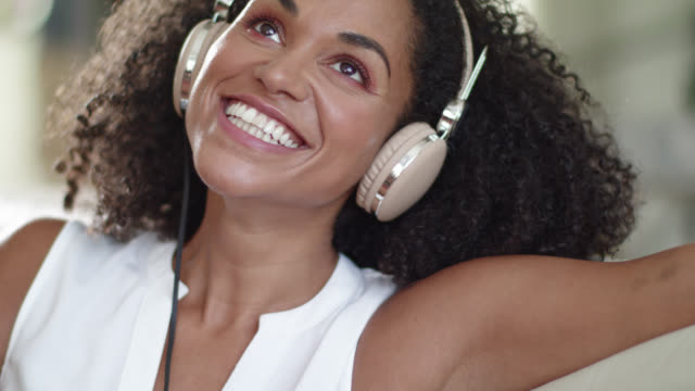 beautiful and sensual black woman is listening to music using her stylish headphones in beauty light and takes down the headphones. - armpit stock videos and b-roll footage