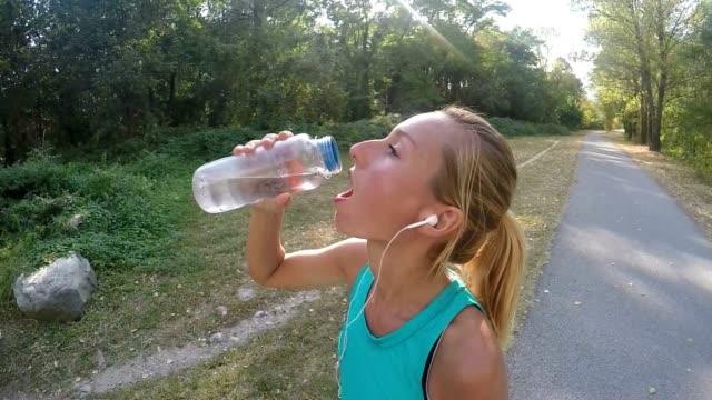 Schöne und sportliche junge Frau Trinkwasser nach dem Joggen im freien