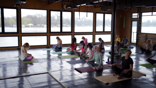 beautiful and young people practicing yoga with slow movements of their body, self-awareness and tranquility in yoga studio - cross legged stock videos & royalty-free footage