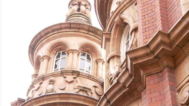 Beautiful arched windows decorate a circular tower on a Victorian buildings in Leeds. Available in HD.