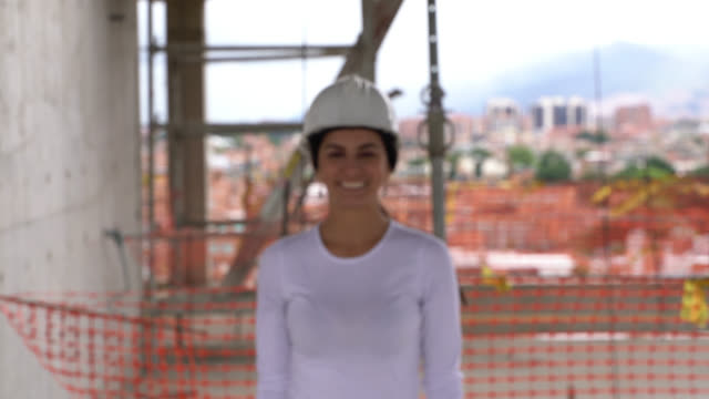 vídeos de stock e filmes b-roll de beautiful architect at a construction site walking towards the camera looking at it smiling - arquiteta