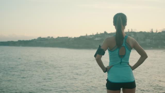 Schöne asiatische Sportler mit Blick auf das Meer (Zeitlupe)