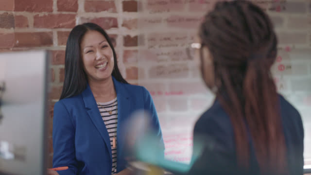 beautiful asian businesswoman smiles as she socializes with a fellow employee - employee stock videos & royalty-free footage