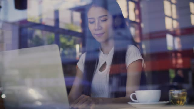 beautiful asian female freelancer using her laptop and working at coffee shop viewed through glass with reflections - freelance work stock videos & royalty-free footage