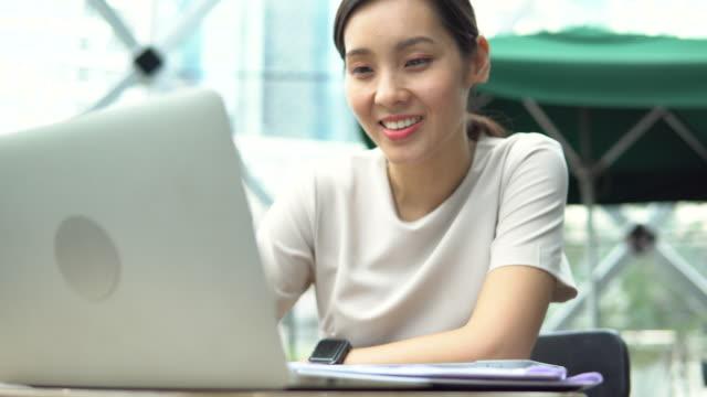 vídeos de stock, filmes e b-roll de bela freelancer asiática usando seu laptop e trabalhando - protetor de ouvido