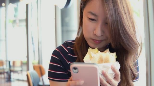 ランチタイムに友達とおしゃべりする美しいアジアの女の子 - 食べ物 サンドイッチ点の映像素材/bロール
