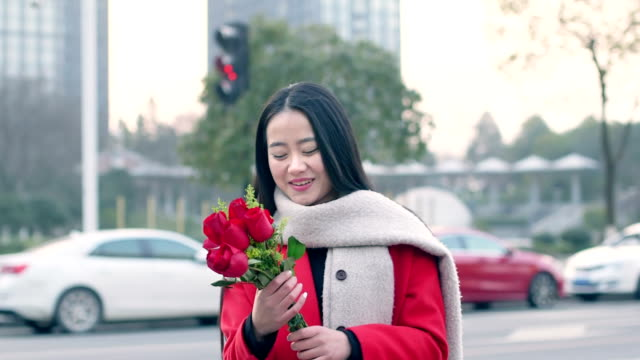 beautiful asian girl holding bunch of red flower