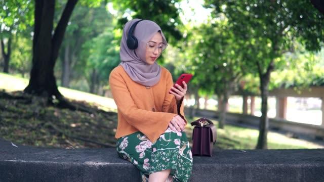 schöne asiatische mädchen hören podcast im park - religiöse kleidung stock-videos und b-roll-filmmaterial