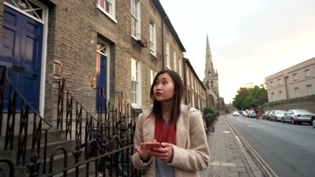 beautiful asian girl use mobile app map for explore city on vacation - cambridge england stock videos and b-roll footage
