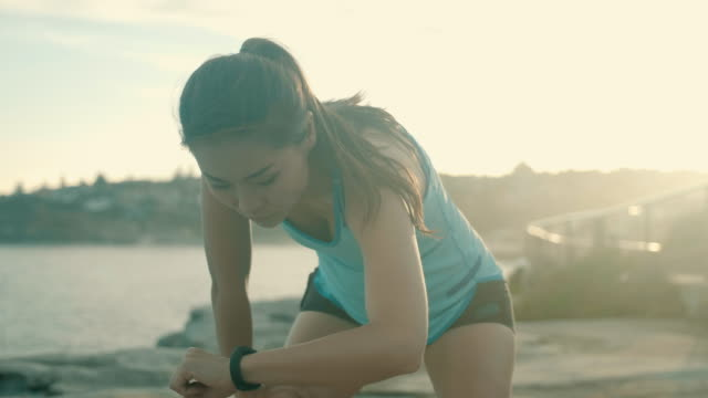 beautiful asian runner checking smart watch - healthy lifestyle stock videos & royalty-free footage
