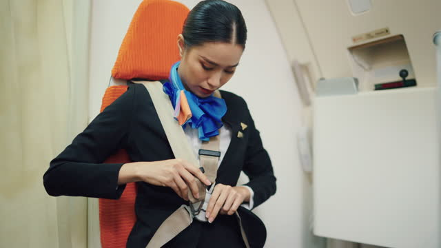 beautiful asian stewardess airline in uniform fasten seatbelt in aircraft on a plane. - aerospace stock videos & royalty-free footage