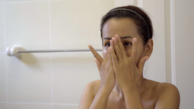 beautiful asian woman applying cream and massage her face with herself. - skin care stock videos & royalty-free footage