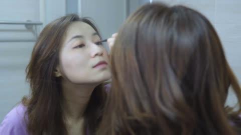 鏡の前で化粧をしている美しいアジアの女性 - mirror点の映像素材/bロール
