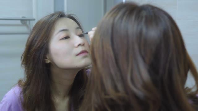 鏡の前で化粧をしている美しいアジアの女性 - 鏡点の映像素材/bロール
