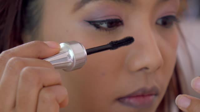Beautiful Asian woman applying mascara