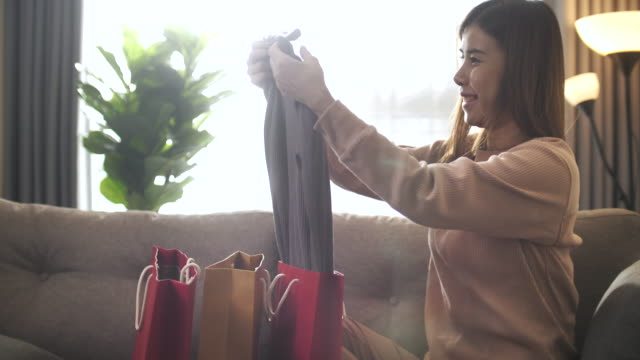 beautiful asian woman at home receiving a parcel and opening shopping bag very happy - shopping bag stock videos & royalty-free footage