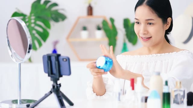 beautiful asian woman blogger is showing how to make up and use cosmetics. in front of the smartphone to recording vlog video live streaming at home.business online influencer on social media concept. - korean ethnicity stock videos & royalty-free footage