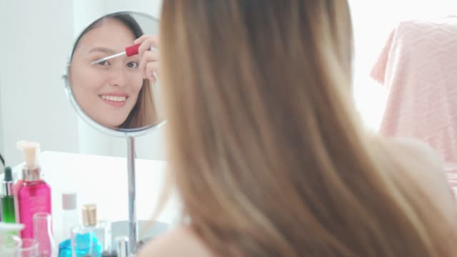 beautiful asian woman blogger is showing how to make up and use cosmetics. in front of mirror at home.business online influencer on social media concept. - mirror stock videos & royalty-free footage