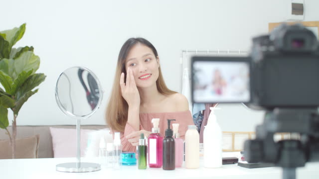beautiful asian woman blogger is showing how to make up and use cosmetics. in front of the camera to recording vlog video live streaming at home.business online influencer on social media concept. - korean ethnicity stock videos & royalty-free footage
