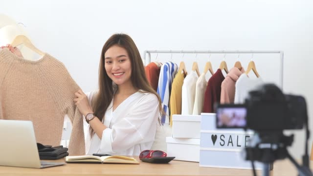 beautiful asian woman blogger is showing shopping clothes and dress. in front of the camera to recording vlog video live streaming at home.business online influencer on social media concept. - stream stock videos & royalty-free footage