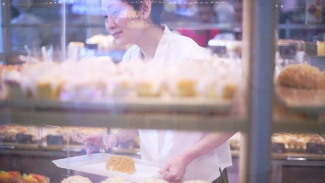 beautiful asian woman chooses bread in the bakery department in the supermarket. healthy eating concept - cream cake stock videos & royalty-free footage