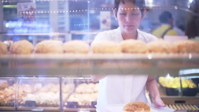 beautiful asian woman chooses bread in the bakery department in the supermarket. healthy eating concept - market retail space stock videos & royalty-free footage