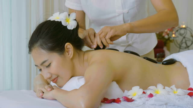 vídeos de stock e filmes b-roll de beautiful asian woman enjoying hot stone massage treatment - articulação humana
