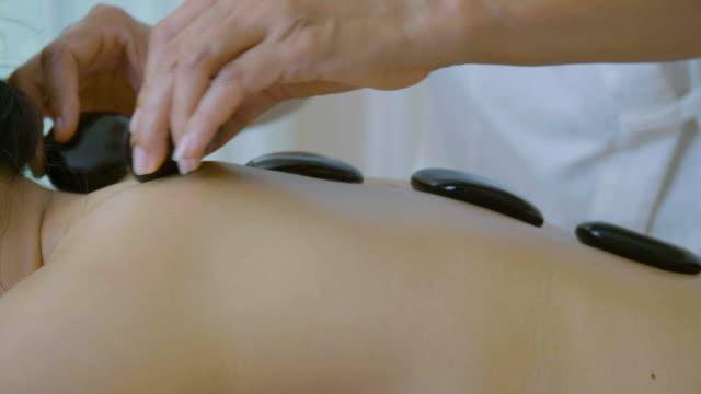 vídeos y material grabado en eventos de stock de ds: hermosa mujer asiática tratamiento de masaje de piedra caliente disfrutando - masajista