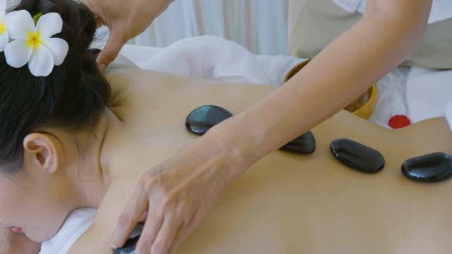 ds: 美しいアジア女性楽しむホット石マッサージ治療 - 人間の関節点の映像素材/bロール