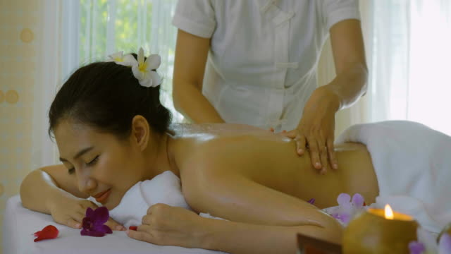 beautiful asian woman enjoying massage therapy with essential oils - massage oil videos stock videos and b-roll footage