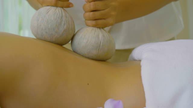 vidéos et rushes de ds: belle femme asiatique bénéficiant de massage thaï herbal compress - masseur
