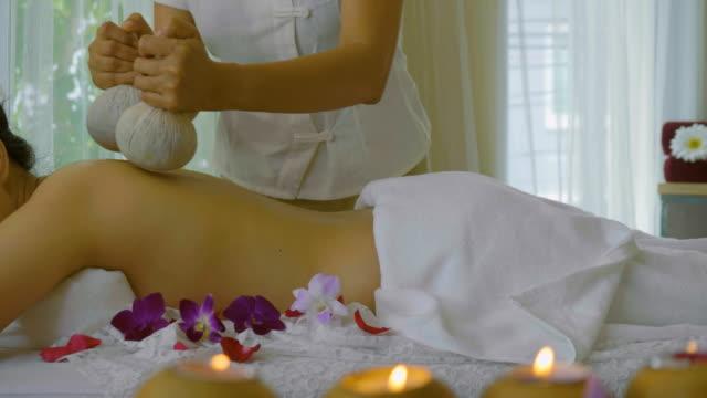 ds : beautiful asian woman enjoying thai herbal compress massage treatment - dorso umano video stock e b–roll