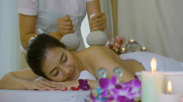 ds: vacker asiatisk kvinna njuter av thailändska växtbaserade compress massagebehandling - hälsosalong bildbanksvideor och videomaterial från bakom kulisserna