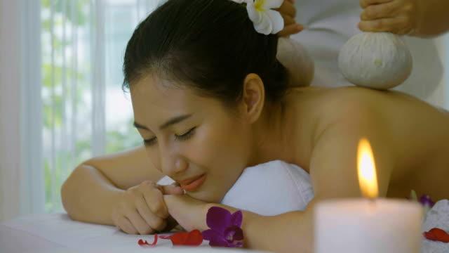 vidéos et rushes de belle femme asiatique bénéficiant de massage thaï herbal compress - masseur
