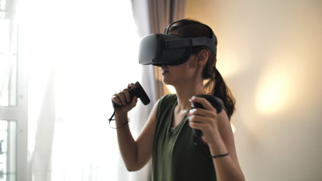 beautiful asian woman exercising with a vr headset at home - 25 29 years stock videos & royalty-free footage