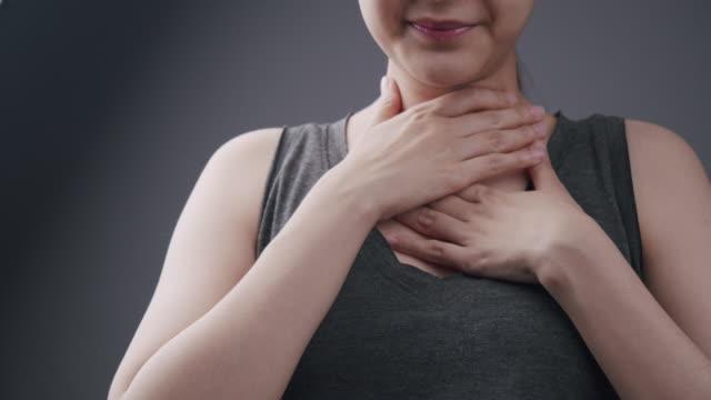 vacker asiatisk kvinna mår dåligt på halsen och svårt att svälja som var sjuk av förkylning och influensa. vuxna kvinnor som lider av körtelinflammation.hals smärta, sjukdom, sjukvård och medicinsk - människohals bildbanksvideor och videomaterial från bakom kulisserna