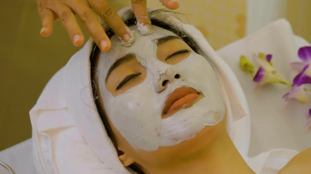 beautiful asian woman having facial mask at beauty salon - facial massage stock videos and b-roll footage