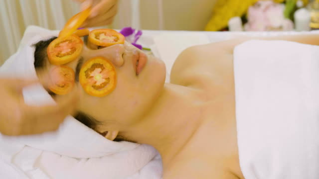 vídeos de stock e filmes b-roll de beautiful asian woman having facial mask at beauty salon - máscara facial