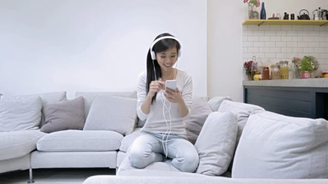 Beautiful asian woman having fun listening music