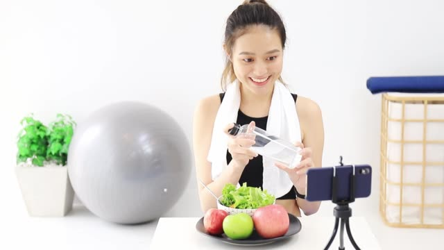 beautiful asian woman healthy blogger is showing apple fruite and clean diet food. in front of the smartphone to recording vlog video live streaming at home.fitness influencer on social media online. - teenage girls stock videos & royalty-free footage