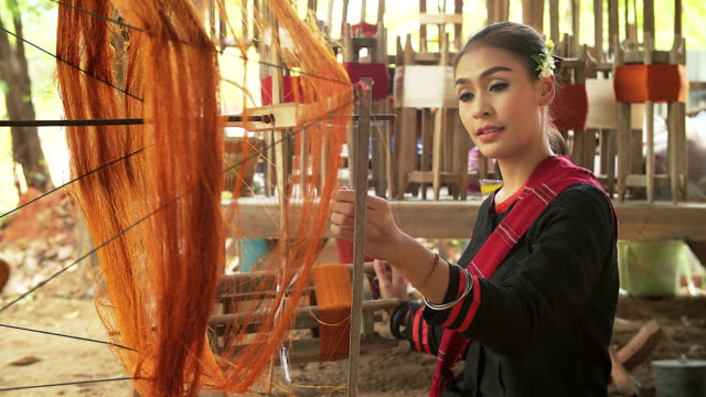 Beautiful asian woman is weaving cotton with a traditional tools.