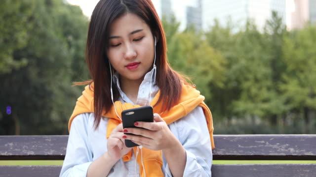 4K: schöne asiatische Frau Musik hören unter Sonne Streulicht im Park, Shanghai, China