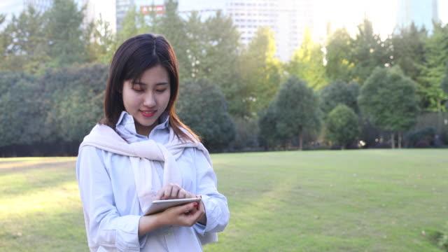 stockvideo's en b-roll-footage met 4k: mooie aziatische vrouw luisteren muziek onder zon flare op park, shanghai, china - 20 24 years