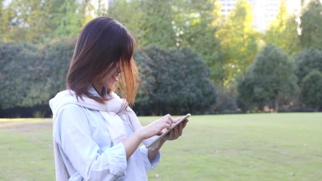 4k: beautiful asian woman listening music under sun flare at park,shanghai,china - 20 24 years video stock e b–roll