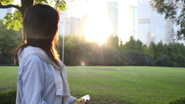 4K: Beautiful Asian woman listening music under sun flare at park,Shanghai,China