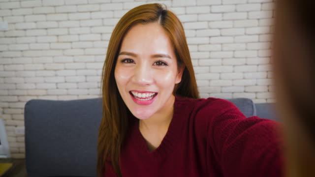 美しいアジアの女性自宅のリビング ルームで selfie を取って赤い服を着た髪の長いブルネット - セルフィー点の映像素材/bロール