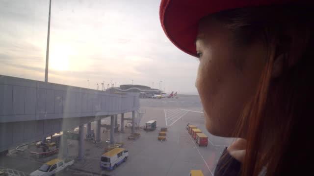 beautiful asian woman looking the plane in the hongkong airport - hong kong international airport stock videos and b-roll footage
