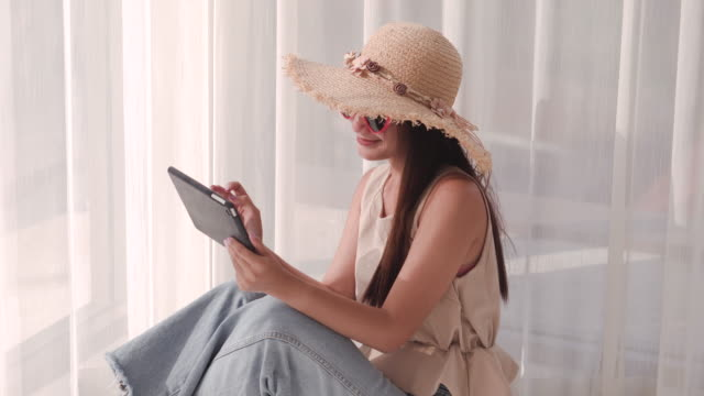 beautiful asian woman play the tablet beside the lighted window. on a summer trip (portrait) - sunny stock videos & royalty-free footage