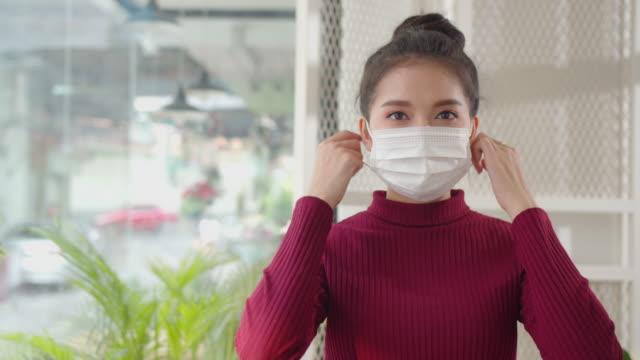 コロナウイルスの発生後に彼女のマスクと笑顔を削除する美しいアジアの女性 - absence点の映像素材/bロール