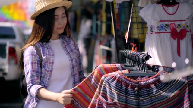 beautiful asian woman shopping on the chatuchak weekend market in the thailand vacation choosing choosing new clothes, looking through hangers with different casual colorful garments on hangers, shopping concept  for herself.business concept. - wardrobe stock videos & royalty-free footage